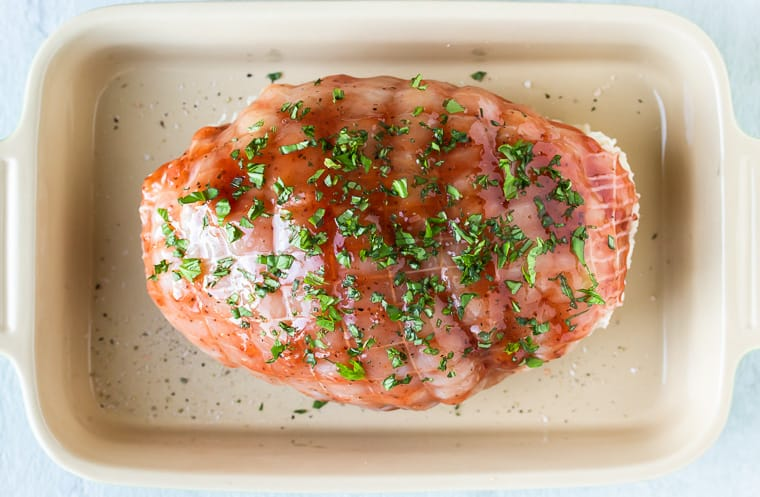 A turkey breast basted in strawberry jam and fresh basil in a baking dish