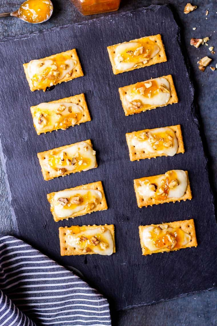Apricot Jam Crackers with Asiago and Walnuts on a slate board over a blue background with a blue and white towel and a spoon of apricot preserves in the background