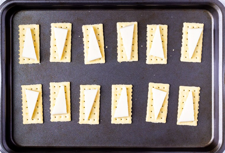 Crackers on a baking sheet each topped with a triangle of asiago cheese