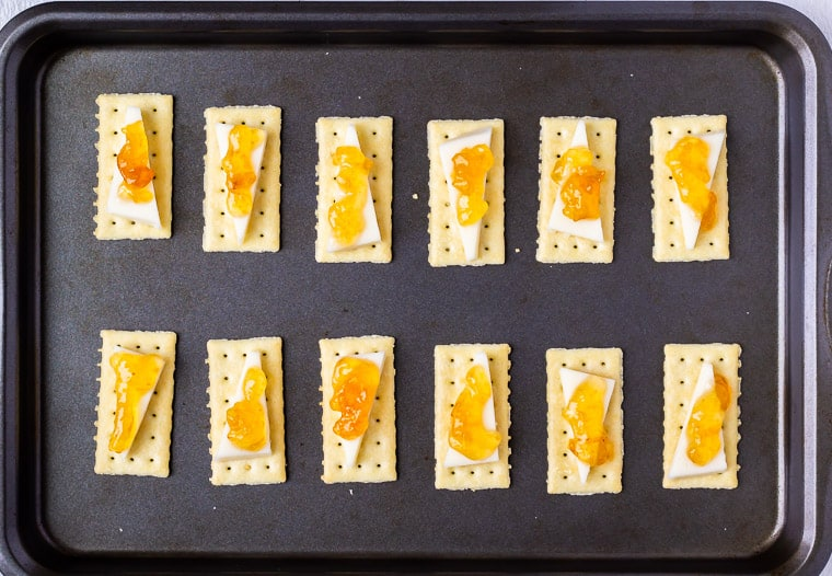 12 crackers on a baking sheet topped with a slice of asiago cheese and apricot jam
