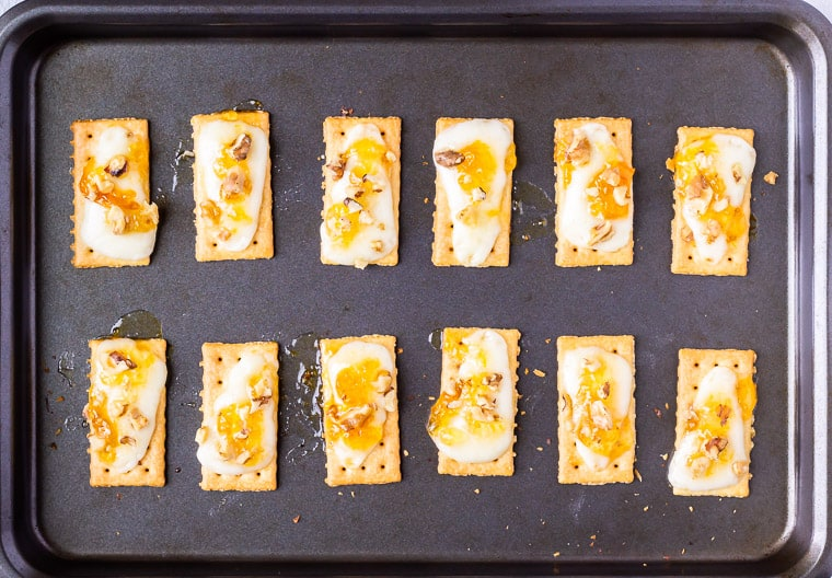 12 crackers on a baking sheet with melted asiago cheese, apricot jam and walnuts
