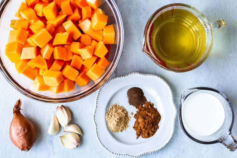 Ingredients needed to make butternut squash soup laid out on a white background