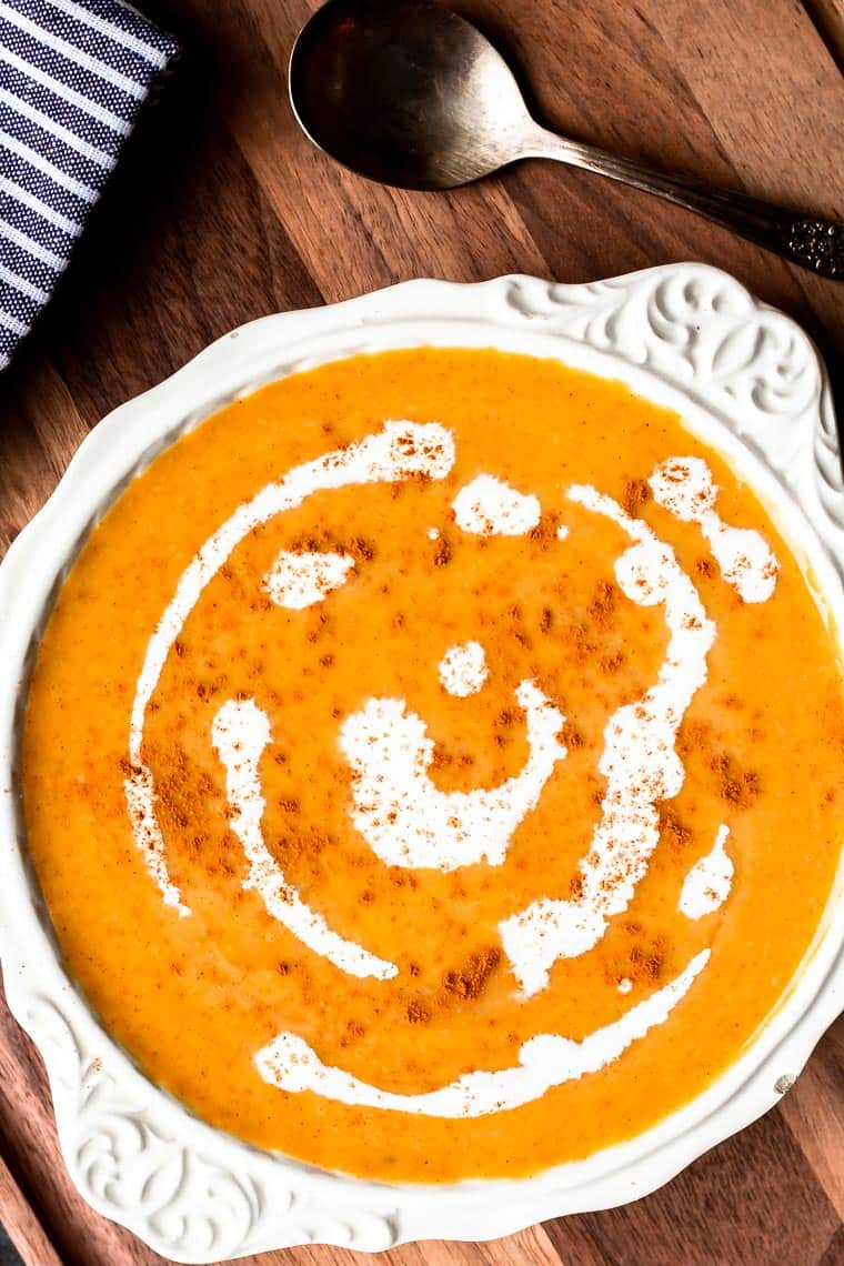 Overhead of a white bowl filled with low carb butternut squash soup on a wood board with a spoon and blue and white striped towel