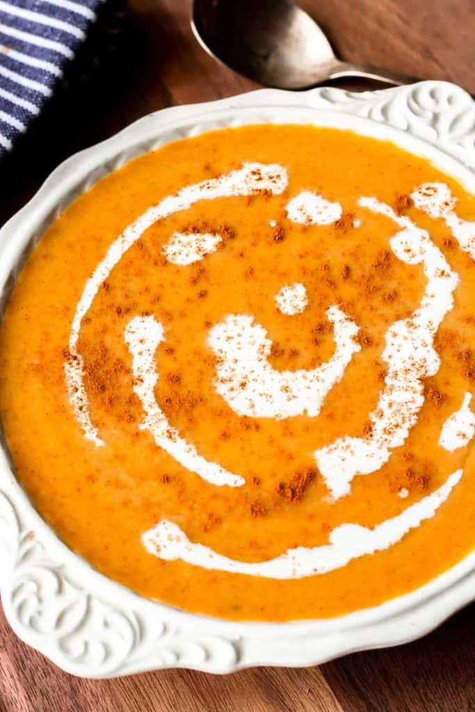 Close up of savory butternut squash soup in a white bowl over a wood board with a spoon and blue and white towel partially showing in the background