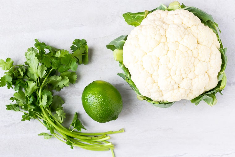 Ingredients needed to make cilantro lime cauliflower rice on a white background