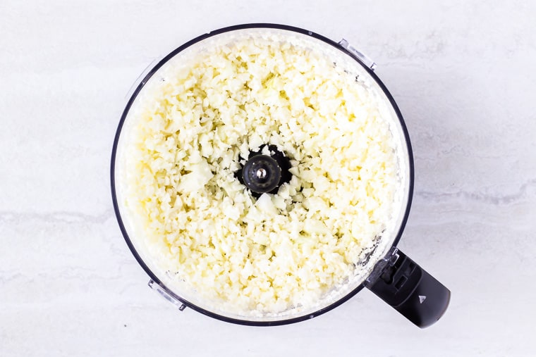 Riced cauliflower in a food processor bowl over a white background