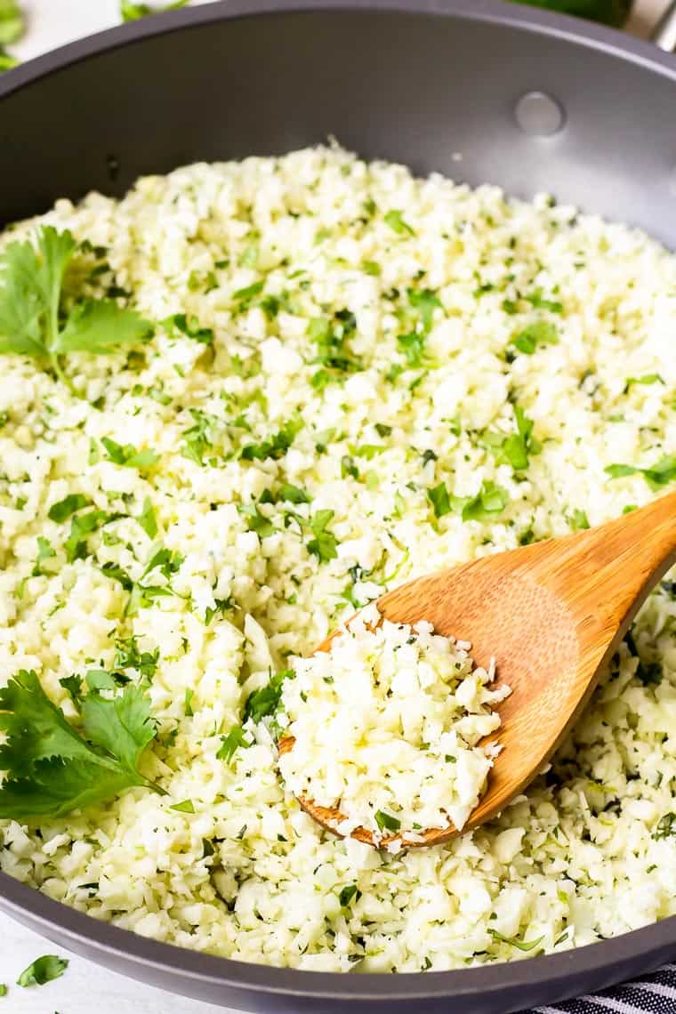 close up of cilantro lime cauliflower rice in a black skillet with a wood spoon