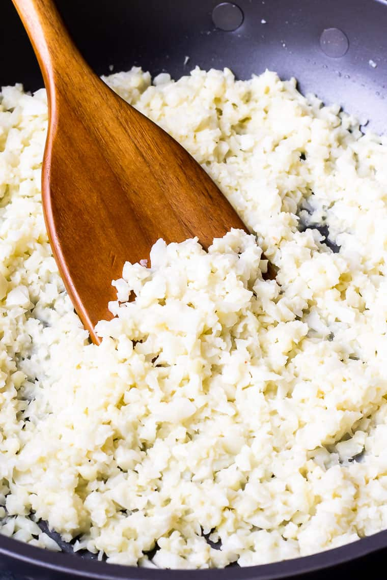 Close up of coconut cauliflower rice in a black skillet with a wood turner
