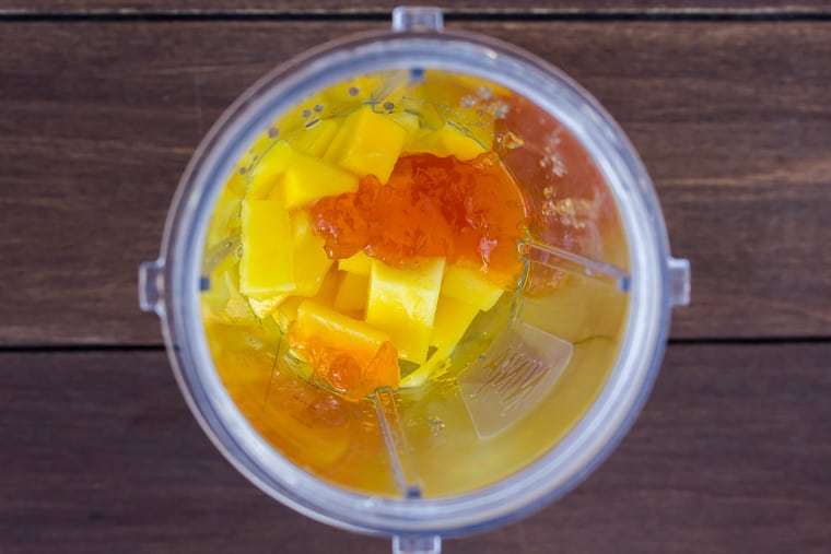 Mango, apricot preserves, and lime juice in a blender cup to be pureed on a wood background