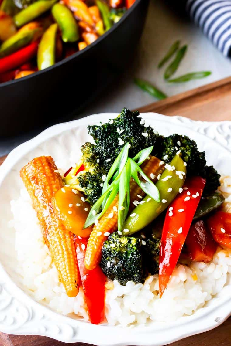 Vegetable Stir Fry on top of rice in a white bowl on a wood board with part of the pan with more vegetables in the background with a blue and white napkin and slices of green onions