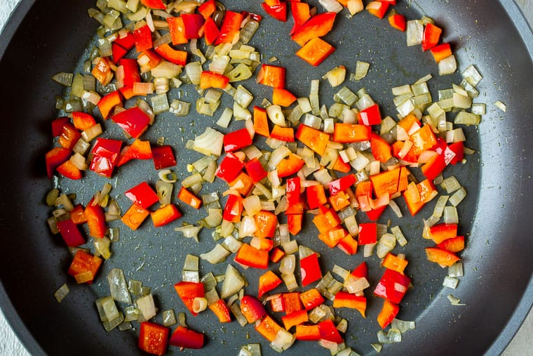Chopped red pepper and shallot cooking in a black skillet