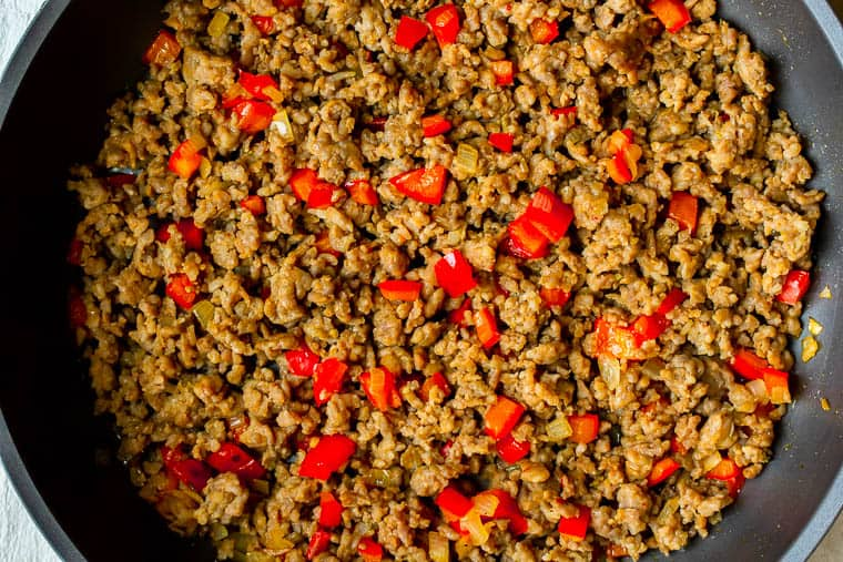 Ground sausage, peppers, and shallot cooking in a black skillet