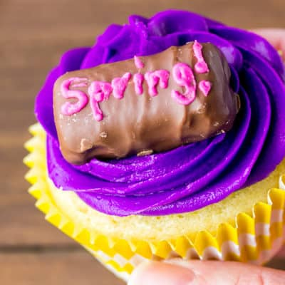 Holding up a vanilla candy cupcake with purple icing and a chocolate candy on top that says spring in pink icing