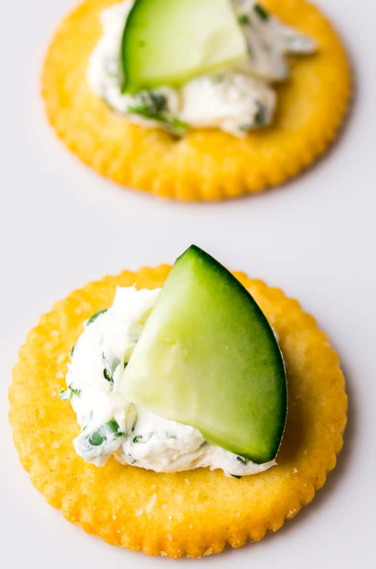 A close up of two round crackers topped with herbed cream cheese and a cucumber piece on a white serving tray