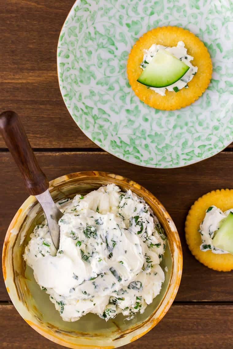 A small brown bowl of Herbed Cream Cheese with a cheese spreader alongside of a green plate with a cracker on it and one next to it on a wood backdrop
