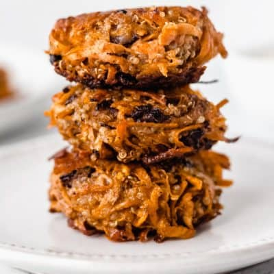 3 sweet potato fritters stacked on top of each other on a white plate over a white background