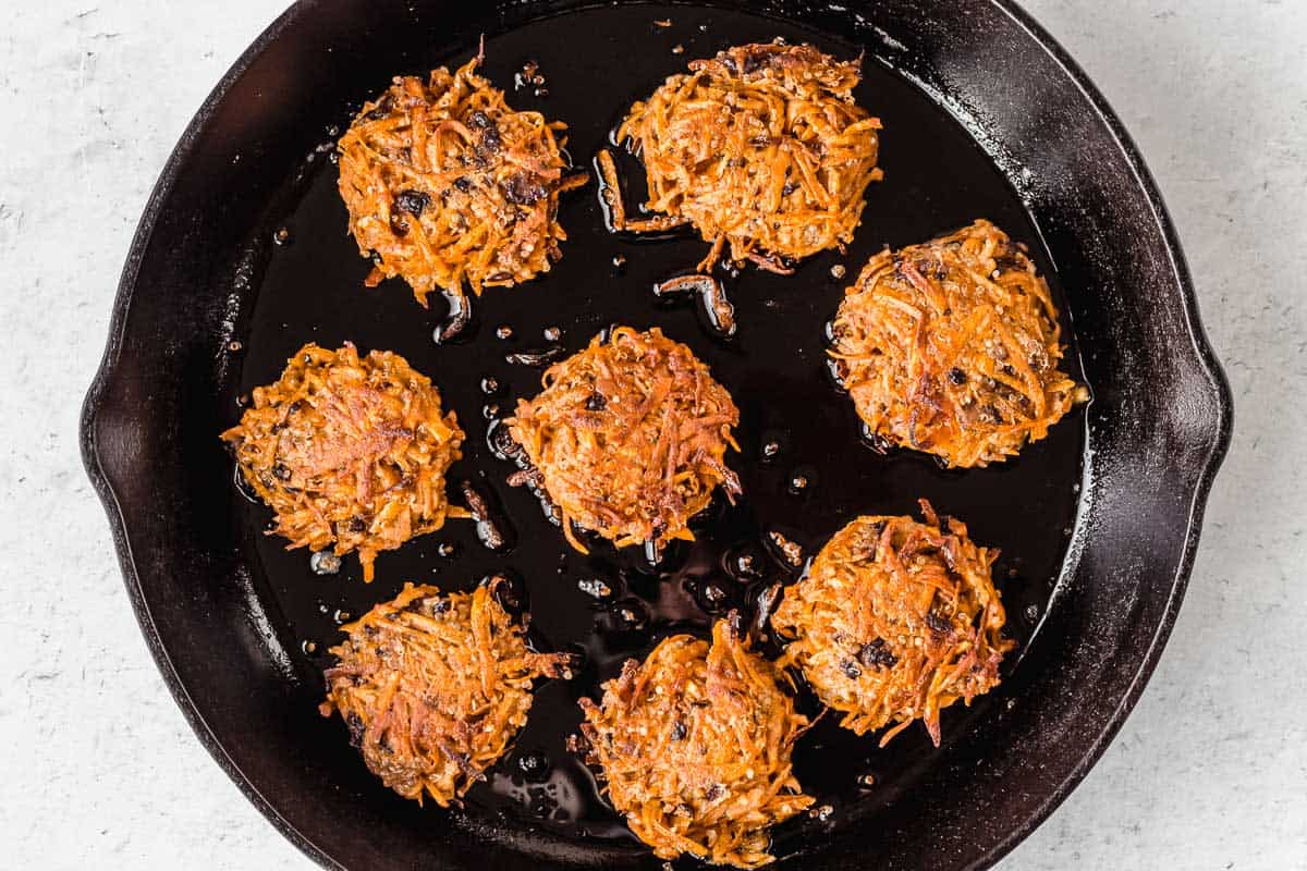 Sweet potato fritters frying in a black cast iron skillet