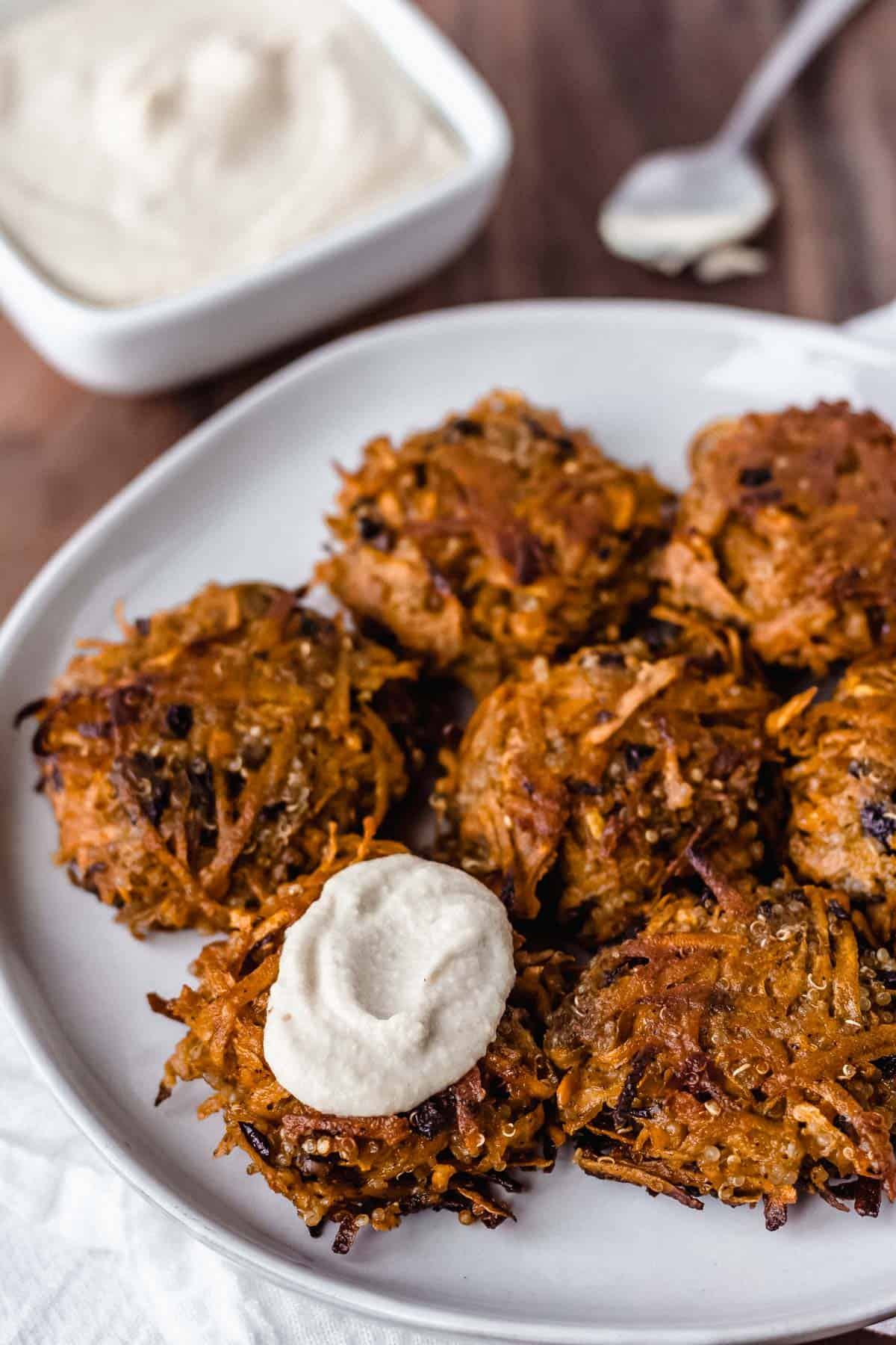 Sweet potato fritters on a round serving plate with one fritter topped with a sauce, a square bowl of sauce and a spoon in the background