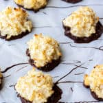 A bunch of chocolate dipped chocolate macaroons on parchment paper