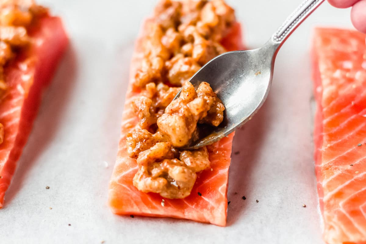 Maple walnuts being spooned onto the top of a salmon fillet