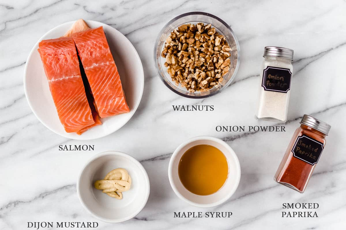 Ingredients for maple walnut salmon with labels on a marble backdrop