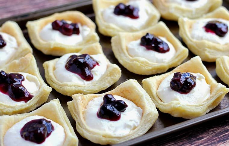A baking sheet full of blueberry sauce topped lemon cheesecake cups