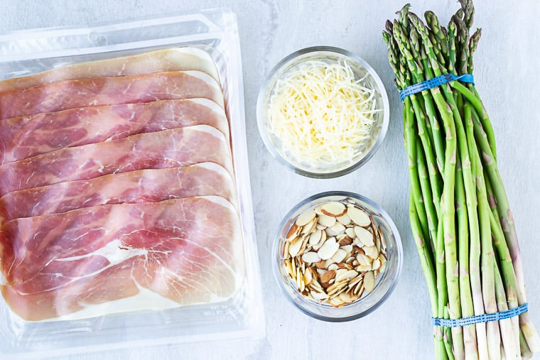 Ingredients needed to make prosciutto wrapped asparagus on a white background