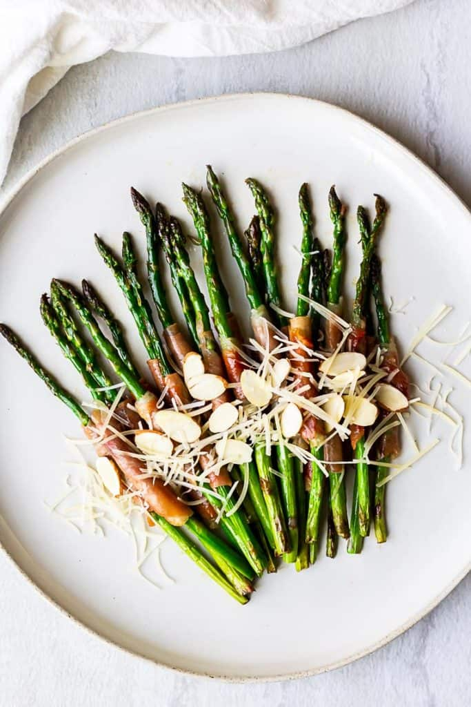 Overhead of prosciutto wrapped asparagus topped with Parmesan cheese and almonds on a white plate over a white background with a white napkin