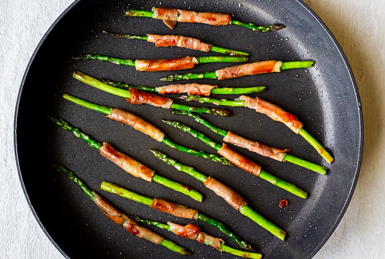 Prosciutto wrapped asparagus cooking in a large, black skillet over a white background