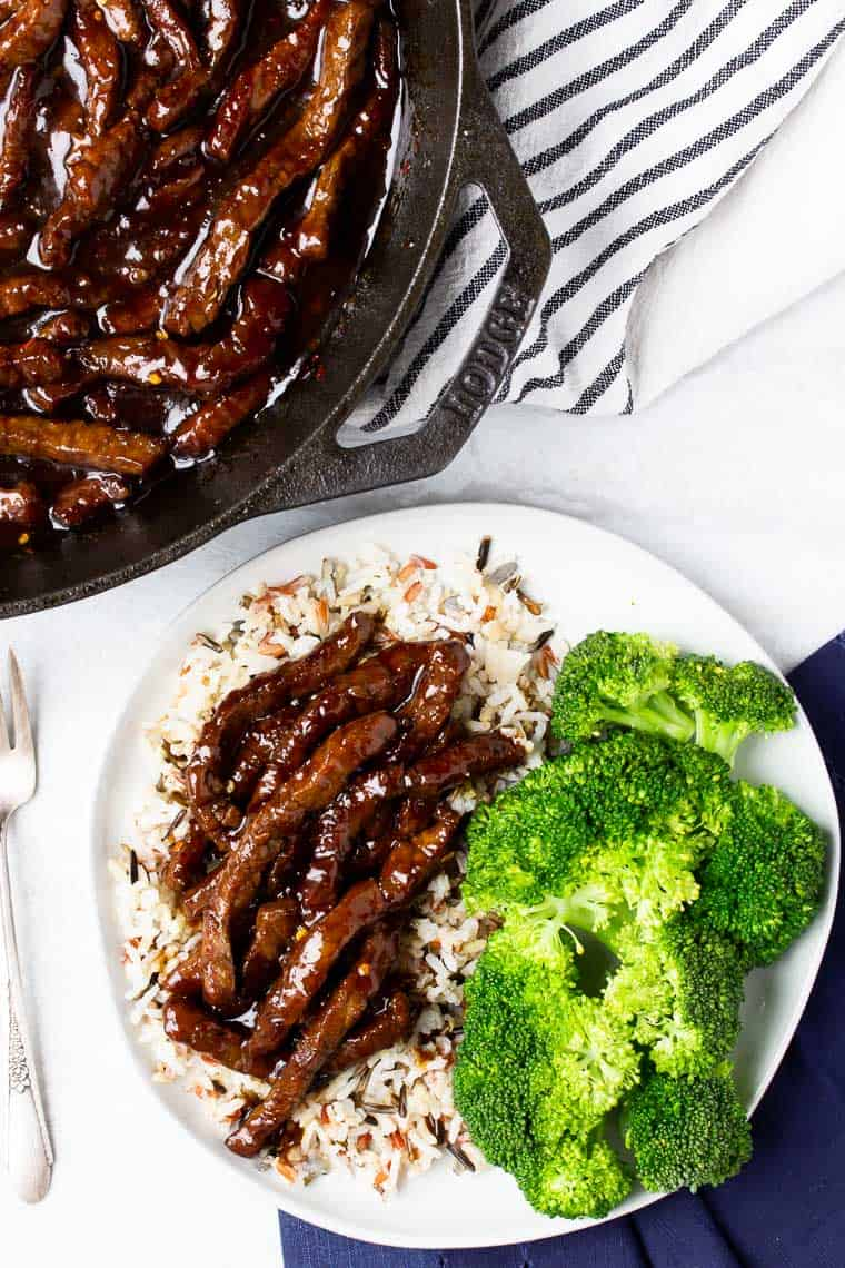 Overhead of spicy mongolian beef on a white plate with rice and broccoli with a cast iron skillet with more beef in it and a black and white napkin over a white background