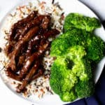 30 Minute Mongolian Beef on a white plate with rice and broccoli and a blue napkin next to it