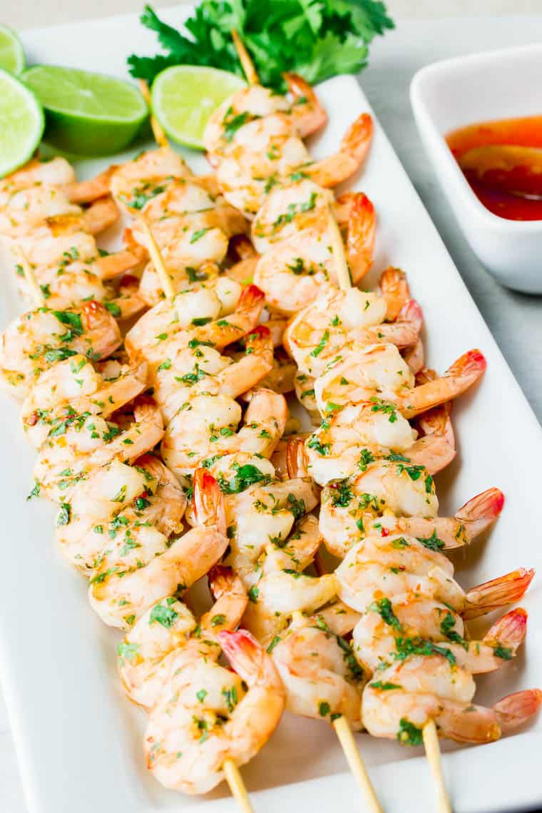 Sweet Chili Lime Shrimp Skewers on a white serving tray with lime, cilantro, and extra sauce on the side