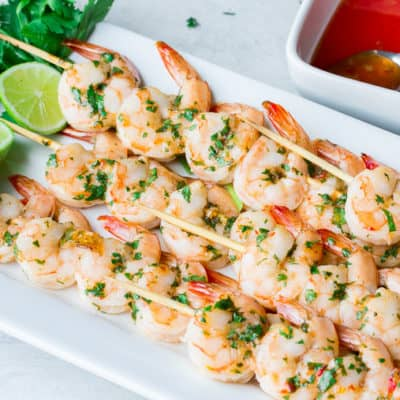 Sweet Chili Lime Grilled Shrimp on a white servign tray with lime, cilantro, and a dish of sweet chili sauce on the side