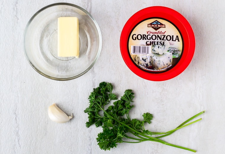 Ingredients for herbed gorgonzola steak butter on a white background