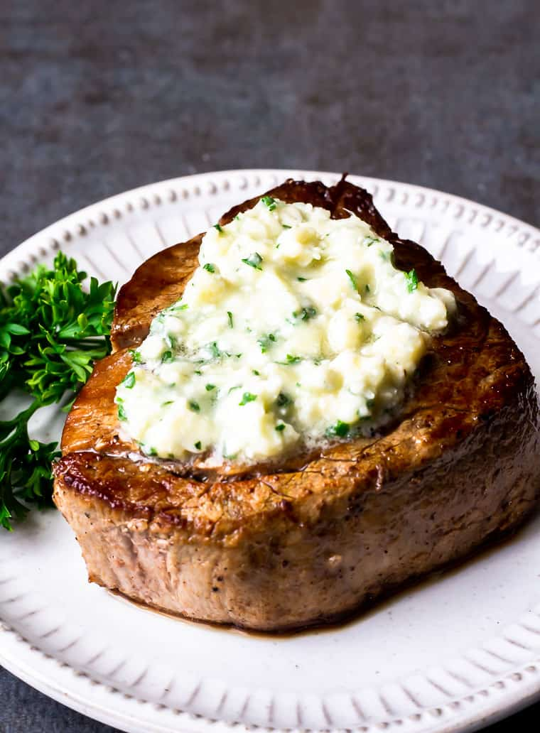 A steak topped with melted herb gorgonzola steak butter on a white plate over a gray background
