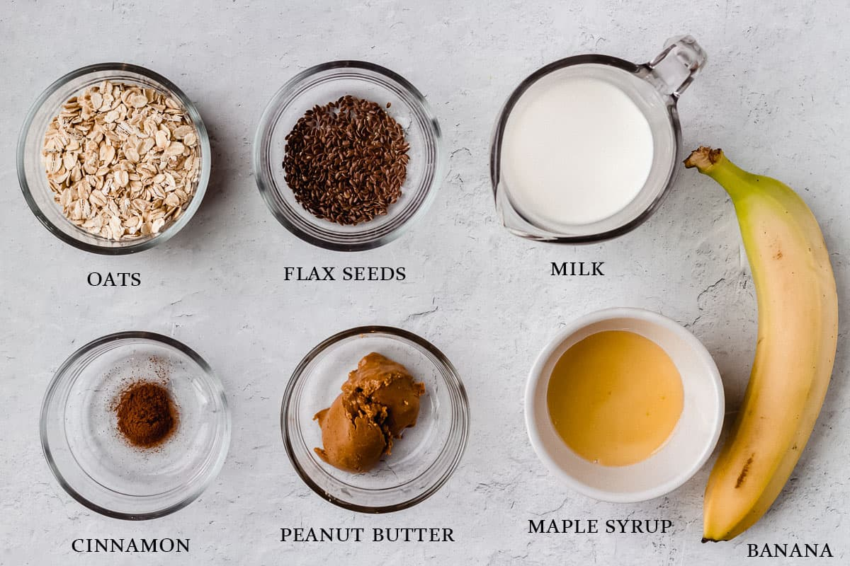 Ingredients to make peanut butter banana overnight oats on a white background with labels