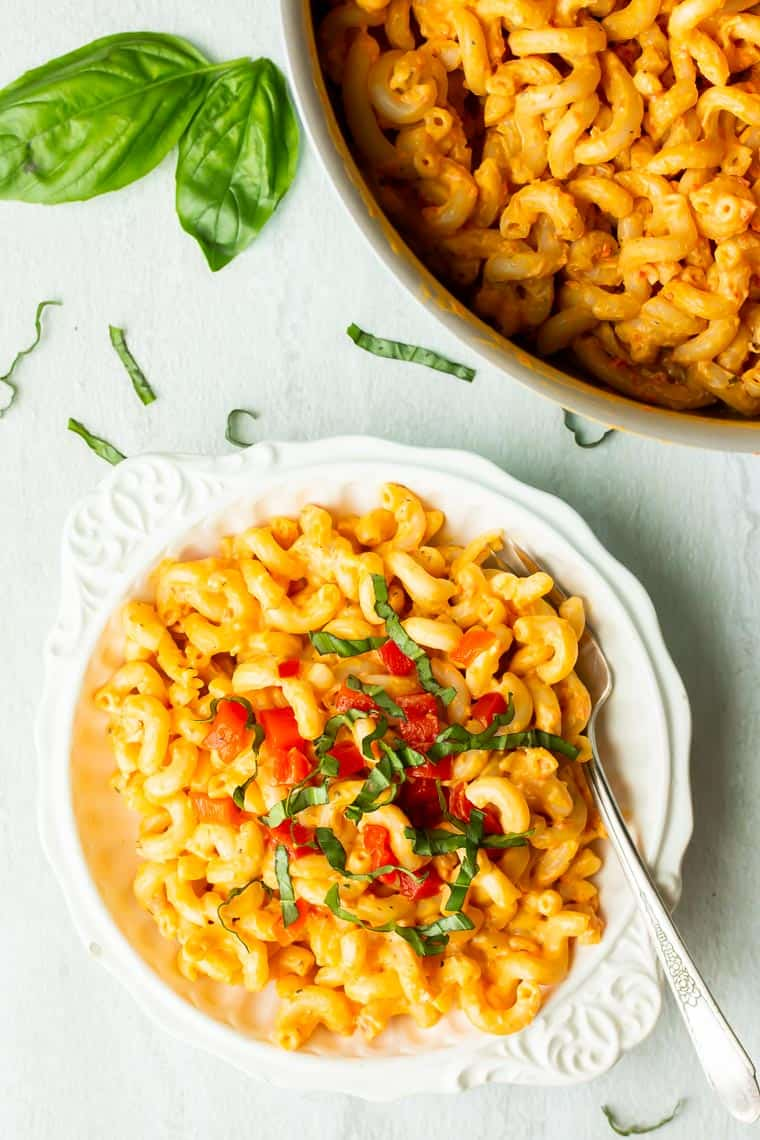Roasted Red Pepper Pasta in a white bowl and a pot over a white background with fresh basil leaves