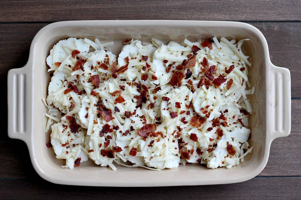 Layer of Cauliflower sliced Topped with Bacon and Cheese n a casserole dish over a wood background