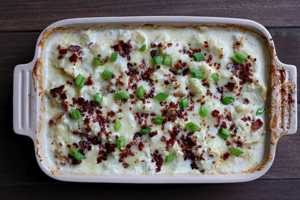 Baked au gratin cauliflower in a rectangular casserole dish over a wood table