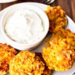 A plate of fried corn cakes with a bowl of sour cream on a wood board with a second plate and 2 forks behind it