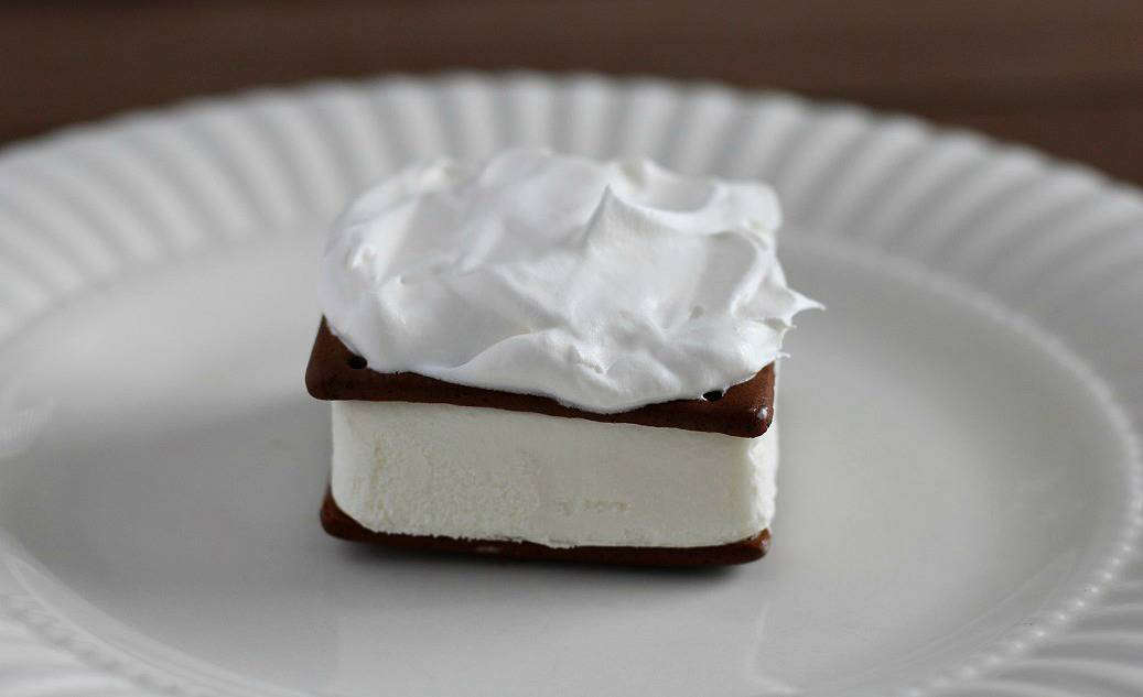 an Ice Cream Sandwich Topped with Whipped Topping on a white plate