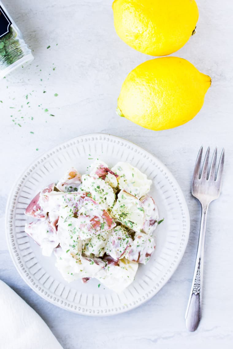 A white plate with potato salad, a fork, 2 lemons, and some dried herbs on a white background