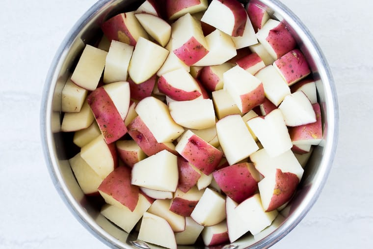 Cut red potatoes in a silver bowl over a white background
