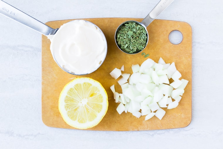 Ingredients needed to make Lemon Tarragon dressing on a cutting board over a white background