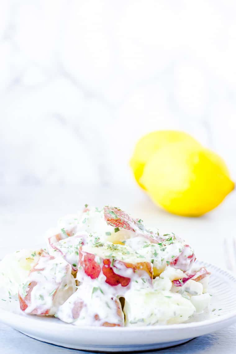 A white plate with Lemon Tarragon Potato Salad with 2 lemons in the background