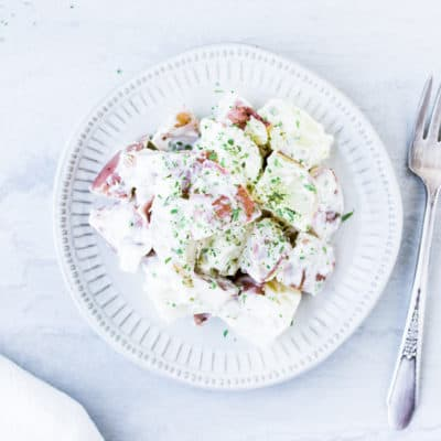 A white plate with Lemon Tarragon Potato Salad with a fork and white napkin on a white background