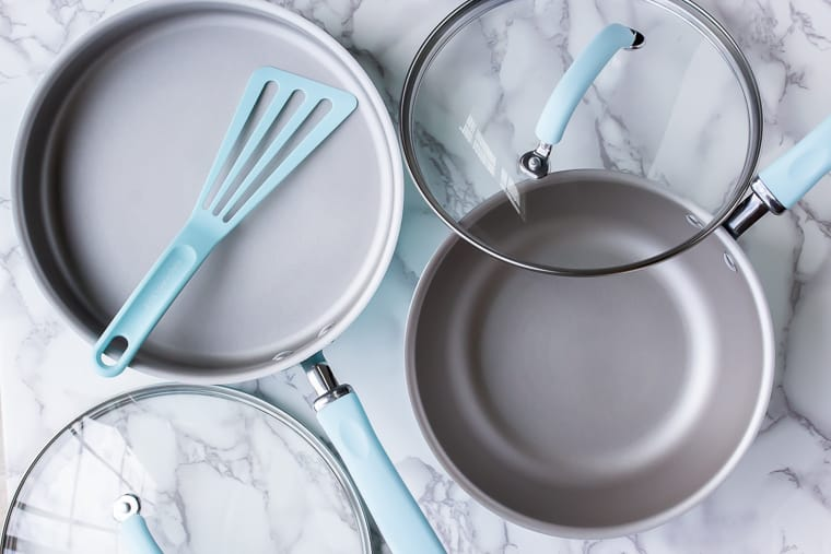 2 Rachael Ray Create Cookware pieces and lids with a spatula over a marble background