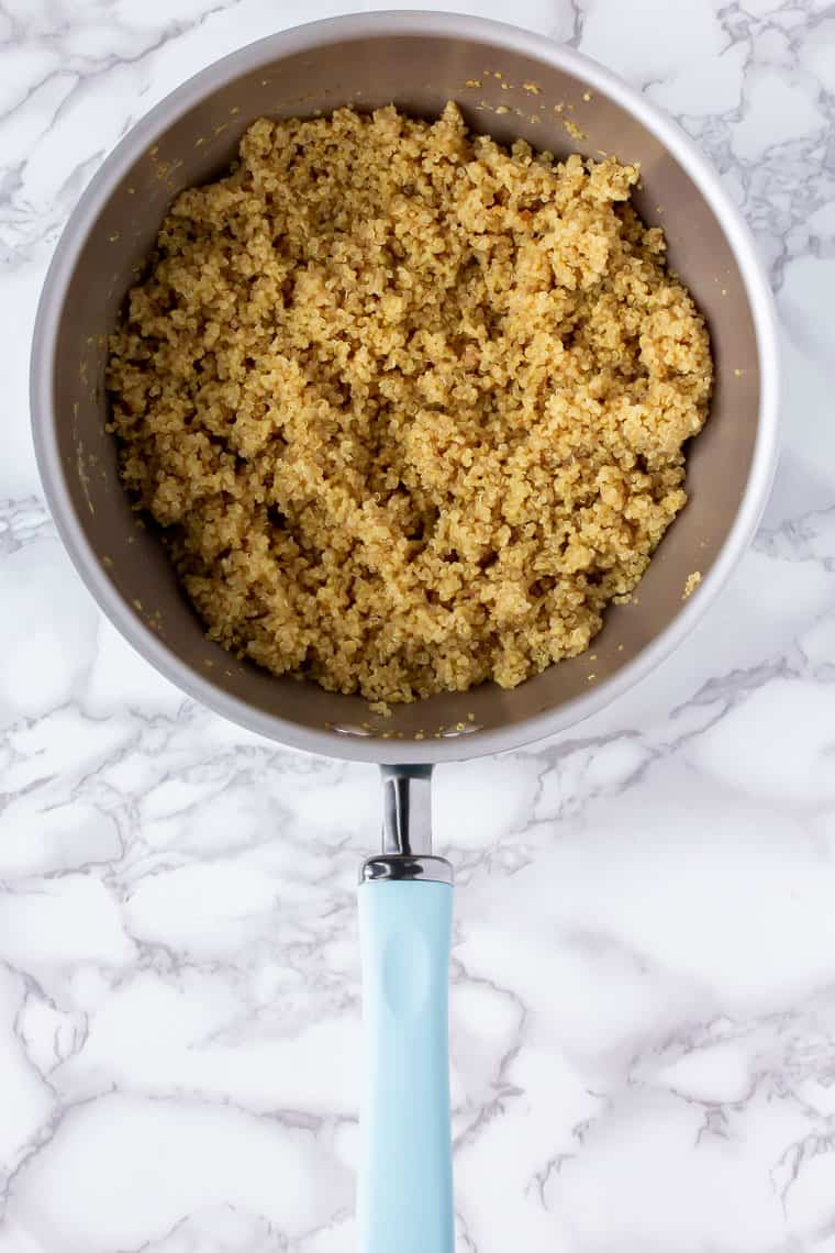Cooked quinoa in a pot with a light blue handle over a marble background