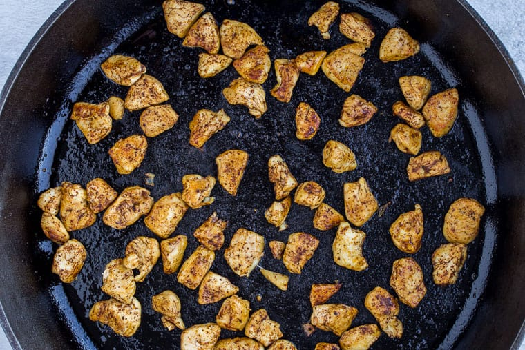 Seasoned chicken chunks cooking in a cast iron skillet
