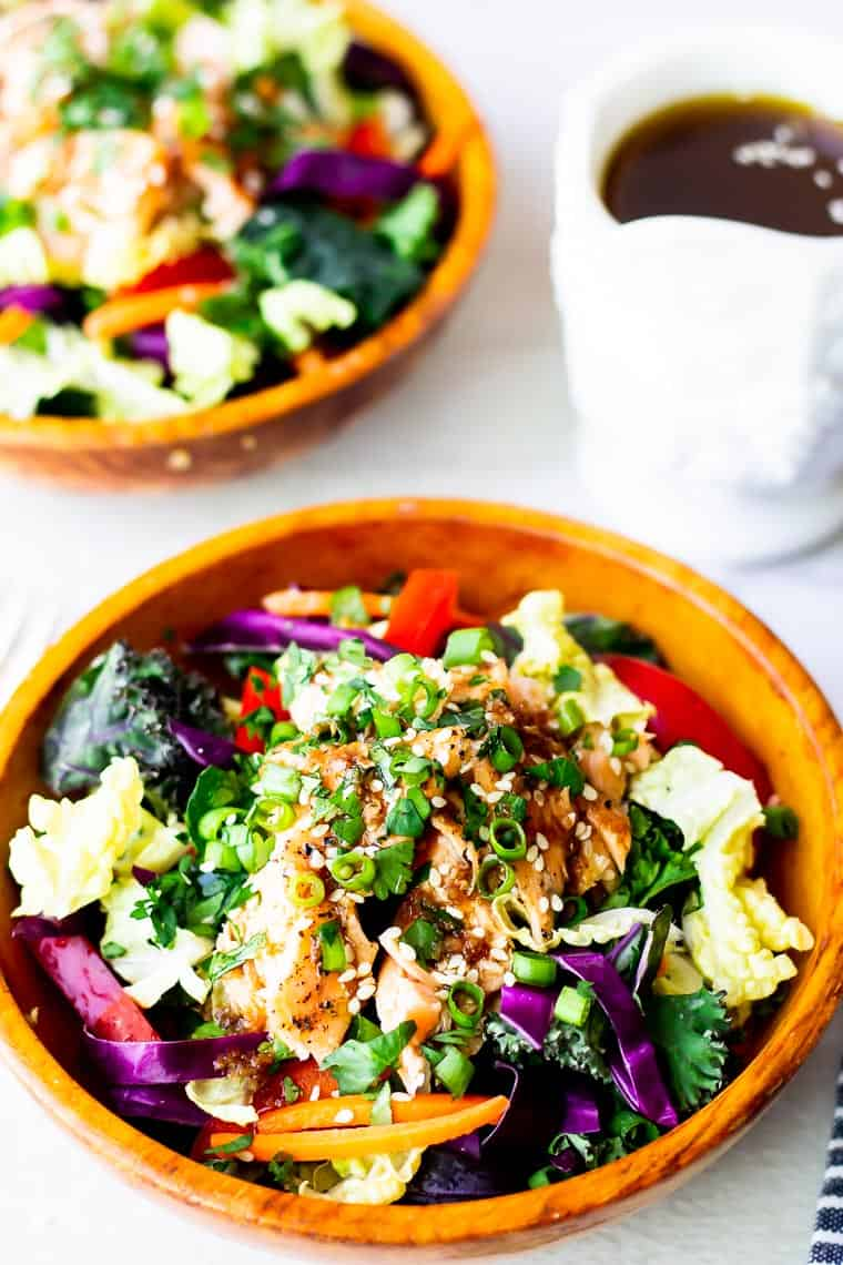 Close up of Thai Salmon salad with a second bowl and pitcher of dressing blurred in the background on a white backdrop